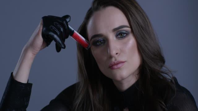 ファッション性の高いモデルはそれで遊んで、彼女の手で赤い口紅を保持しています。ファッションのビデオ。 - リップクリーム点の映像素材/bロール