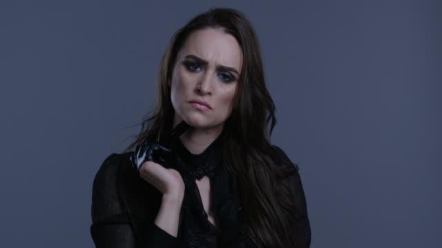 黒革手袋でファッション性の高いモデルは、黒のマスカラー チューブを保持します。ファッション モデル。 - 誘惑点の映像素材/bロール