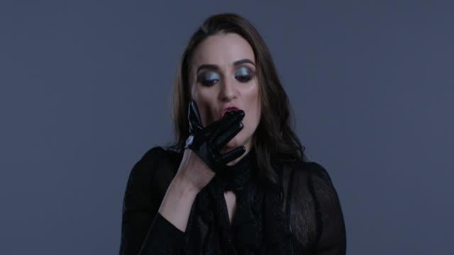 vidéos et rushes de modèle de haute couture en blouson de cuir noir avale la bouteille de vernis à ongles noir. mode vidéo. - crayon à lèvres