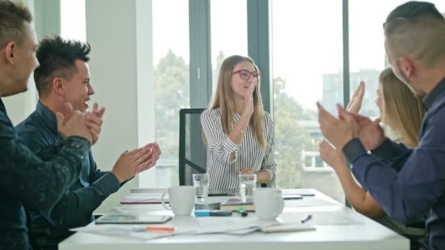 high fives members at a startup in a modern office - достижение стоковые видео и кадры b-roll