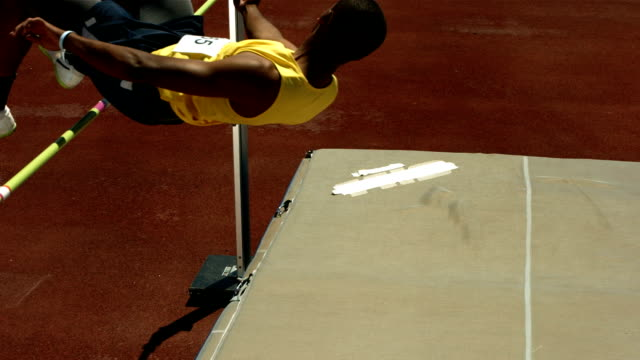 High jumper falling onto mat, slow motion video