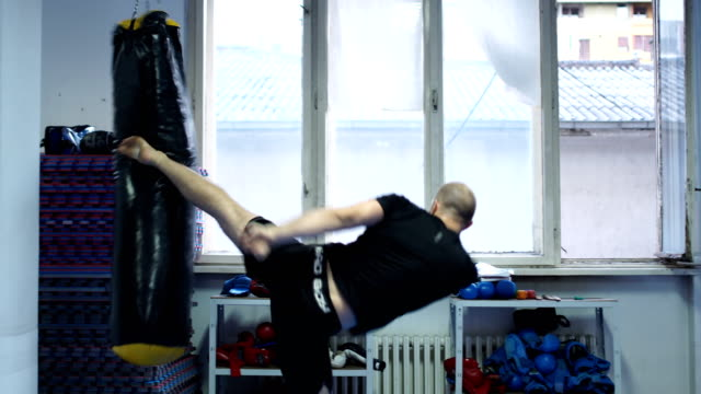 high kick on kickboxing bag - sacco per il pugilato video stock e b–roll
