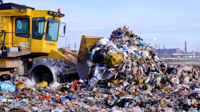 A high pile of trash moved by a landfill truck. Water, air contamination concept. A close view of a landfill compactor moving a large pile of assorted garbage. dump truck stock videos & royalty-free footage