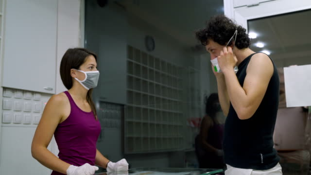 High protection of Corona virus at the gym. Preparing for training:use protective mask and protective gloves. video