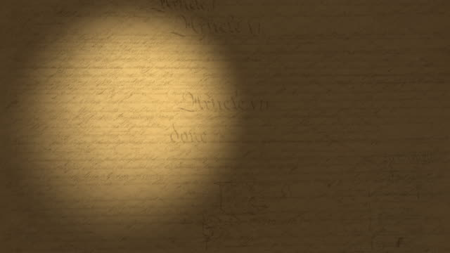 High resolution 4K video of a beam of light moving on the US Constitution pages.