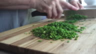istock High resolution video of a senior woman chopping fresh chives, on a wooden cutting board. 1266331392