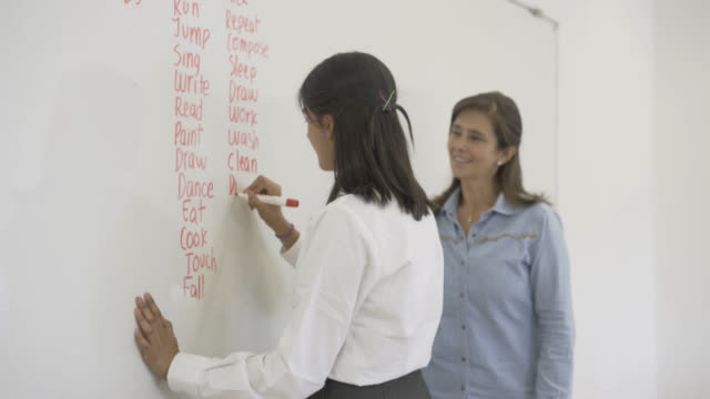 High school female students writing english verbs on the whiteboard video