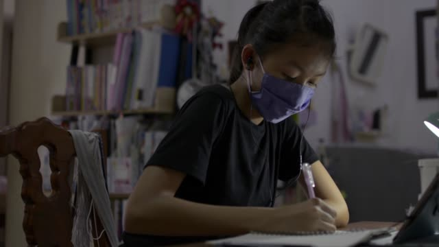 High school girl wearing protective face mask and earphones using digital tablet for lesson online at home.
