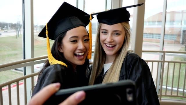 vídeos de stock, filmes e b-roll de graduados do ensino médio tomam selfies - beca