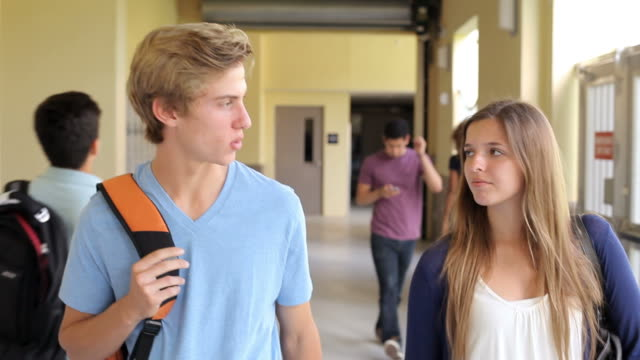 High School Student Couple Walking Along Hallway video