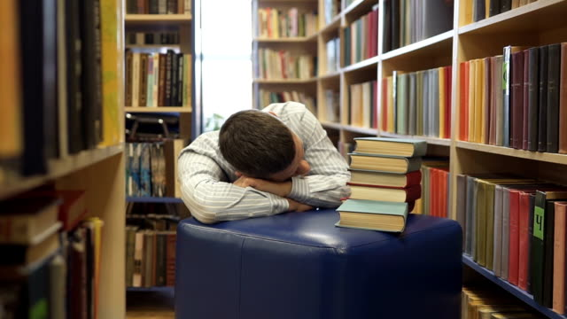 A high school student fell asleep in the library over books. The concept of libraries video