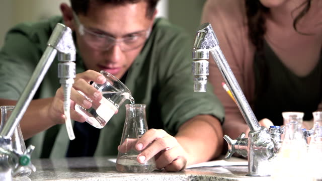high school student in chemistry class pouring liquid - high school stock videos and b-roll footage