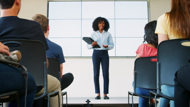 High School Students Applaud Female Teacher Giving Presentation In Front Of Screen