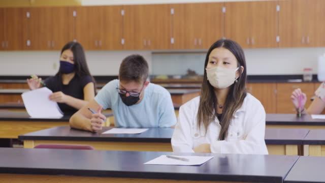 studenti delle scuole superiori in classe che indossano una maschera protettiva per il viso - esame università video stock e b–roll