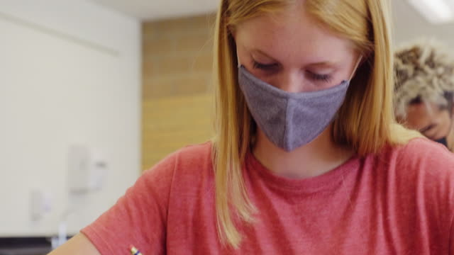 High School Students In Classroom Wearing Protective Face Mask High school students in a classroom, wearing protective face masks to help against spreading infectious disease. educational exam stock videos & royalty-free footage