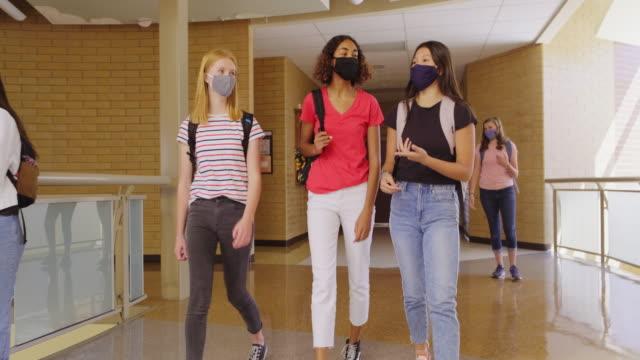 vídeos de stock, filmes e b-roll de estudantes do ensino médio na escola usando máscara facial protetora - adolescência