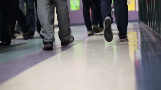 High school students pass each other in the hall walking by lockers in between class. Feet of students passing each other in hall school building stock videos & royalty-free footage