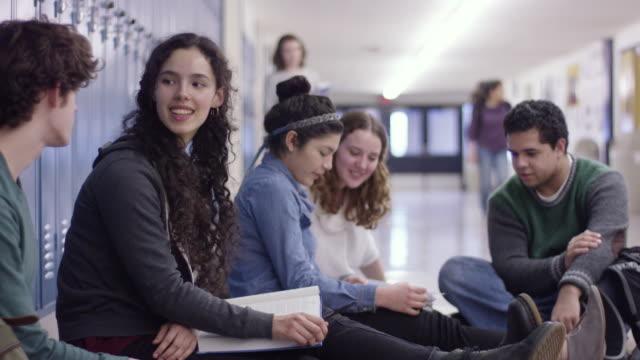 vídeos de stock, filmes e b-roll de estudantes do ensino médio sentado no corredor - armário com fechadura