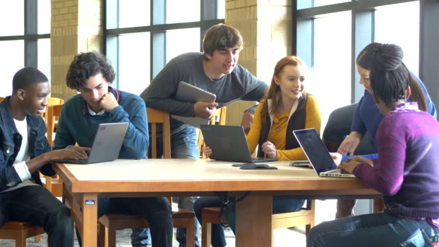 High school students using digital tablets and laptops A group of six multi-ethnic high school students, 15 to 17 years old, working on a project together at the library, using digital tablets and laptops. medium group of people stock videos & royalty-free footage
