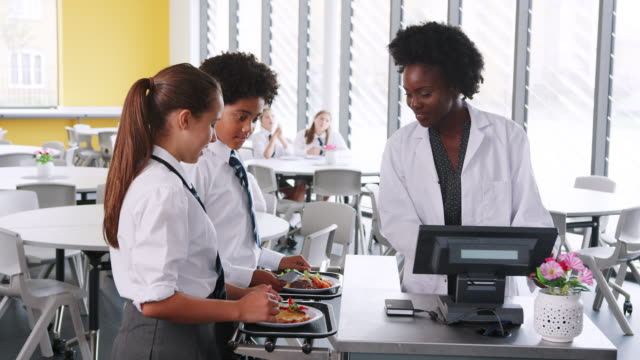 high school students wearing uniform paying for meal in cafeteria - banchi scuola video stock e b–roll