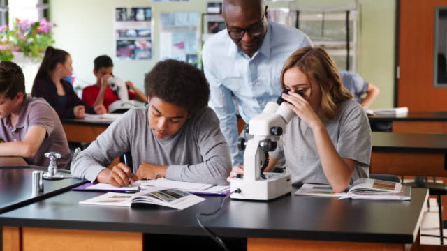 High School Students With Tutor Using Microscope In Biology Class video
