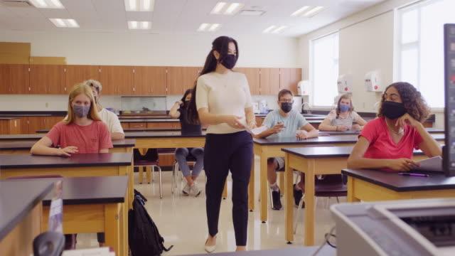 nauczyciel szkoły średniej i uczniowie w klasie noszenie ochronnej maski na twarz - instruktor filmów i materiałów b-roll
