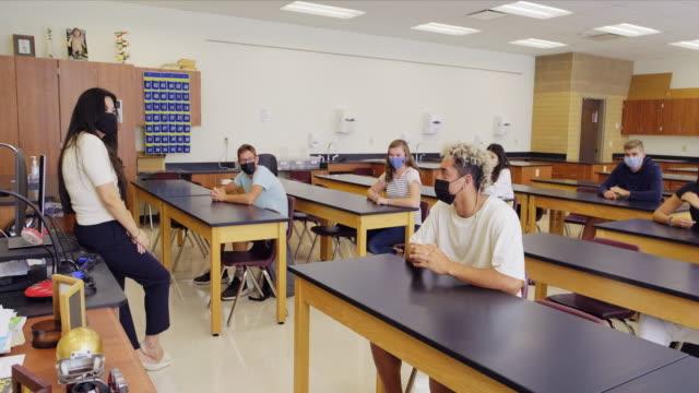 stockvideo's en b-roll-footage met de leraar van de middelbare school en studenten in klaslokaal dat beschermend gezichtsmasker draagt - school