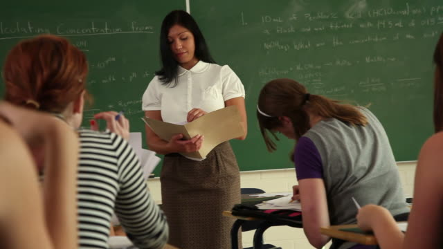 High school teacher passing out papers video