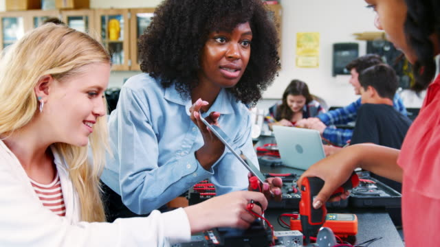 vídeos de stock e filmes b-roll de high school teacher with female pupils building robotic vehicle in science lesson - stem assunto