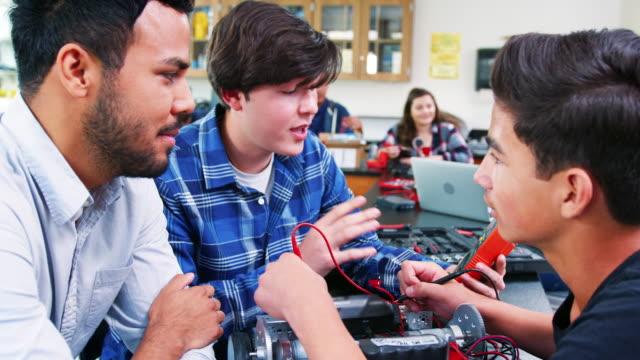 gymnasiallehrer mit männlichen schüler gebäude roboterfahrzeug in wissenschaft lektion - highschool stock-videos und b-roll-filmmaterial