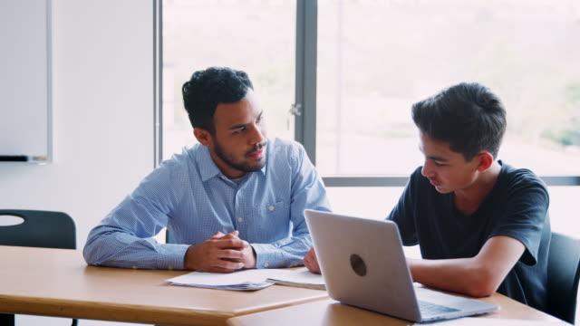 high school lehrer geben männliche schüler einzelunterricht am schreibtisch - nachhilfelehrer stock-videos und b-roll-filmmaterial