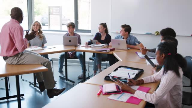 high school lehrer sitzen am schreibtisch und lehre klasse erschossen in slow motion - highschool lehrer stock-videos und b-roll-filmmaterial