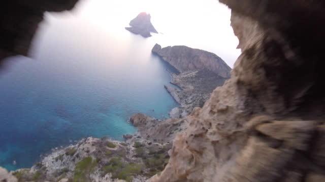 vídeos de stock e filmes b-roll de high speed drone flying through natural rock arch down mountain - ibiza