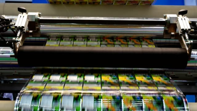 High speed labeling machine in industrial factory. Machine for sticker on product in manufacture. Flexible packaging.