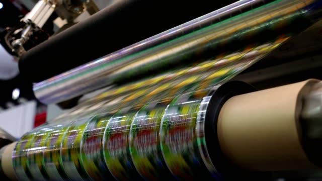 high-speed etikettiermaschine im industriebetrieb. maschine für aufkleber auf produkt in der herstellung. flexible verpackungen. - etikett stock-videos und b-roll-filmmaterial