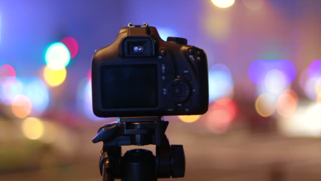 high technology camera on tripod recording city lights, cars and transportation in night time. - bokeh stock videos & royalty-free footage