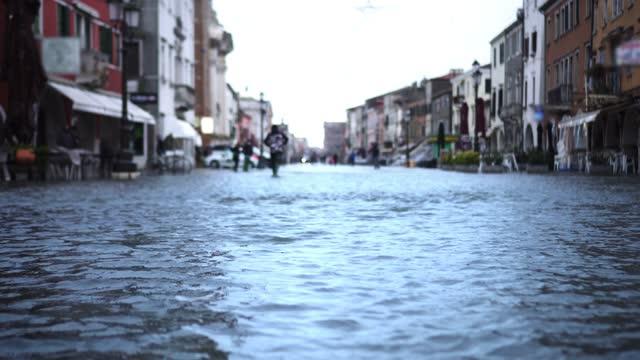 High tide flood water covers narrow Italian old street