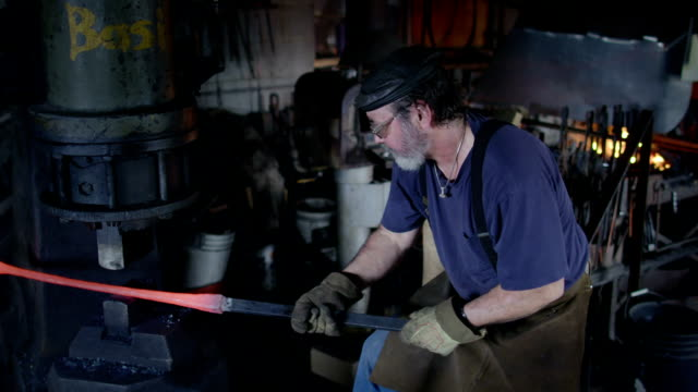 High viewpoint of blacksmith pounding hot iron with industrial hammer video