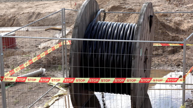 high voltage cable reel in wet dirt - sottosuolo video stock e b–roll