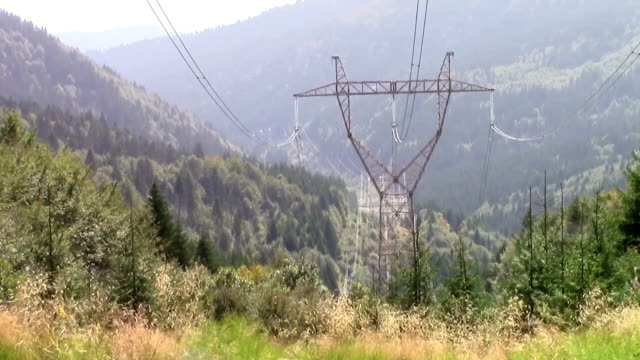 High voltage electrical power lines poles in the mountains carrying electricity through the valley to household and industrial consumers Electrical power lines in the mountains high voltage sign stock videos & royalty-free footage