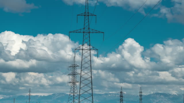 high voltage post tower with blue cloudy sky background - sottostazione elettrica video stock e b–roll