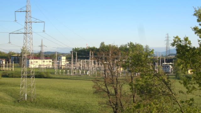 AERIAL: High voltage power lines and electricity power plant in green suburbs video