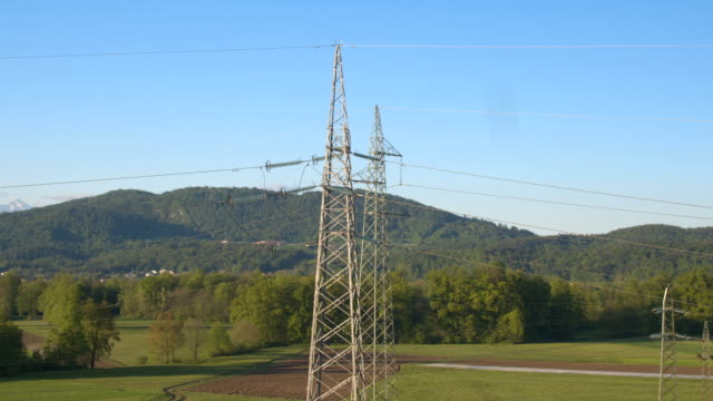 AERIAL: High voltage powerlines and electricity steel pylons next to lush forest video