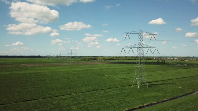High voltage pylons with green fields blue sky and cumulus clouds Filmed in 4K Ultra HD at 25 fps power supply stock videos & royalty-free footage