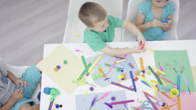 High-Angle Shot of a Preschool Arts and Crafts Class Top-down shot of a group of young children doing arts and crafts with their Black female teacher playroom stock videos & royalty-free footage