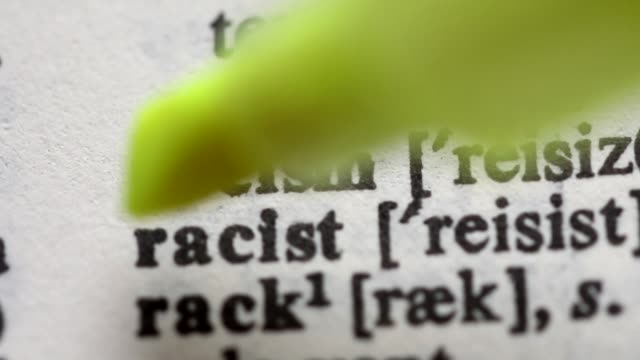 Highlighting the word RACISM definition. Signaling the meaning of being a racist video