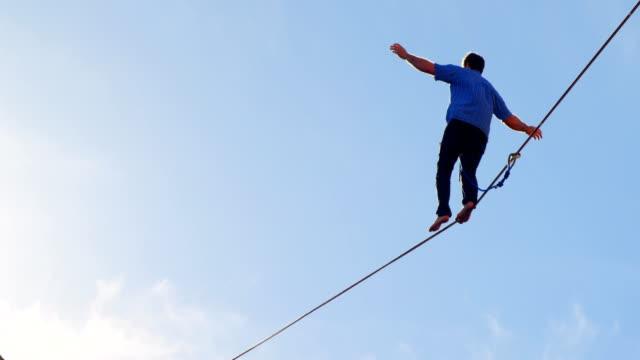 stockvideo's en b-roll-footage met highline atleet lopen op slackline 4k - touw