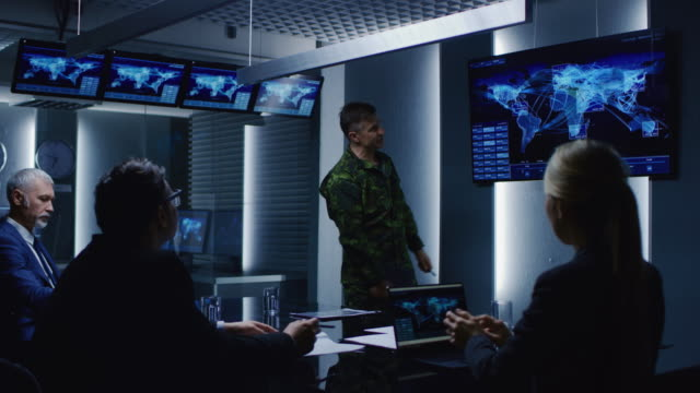 High-Ranking Military Man holds a Briefing to a Team of Government Agents and Politicians, Shows Satellite Surveillance Footage. High-Ranking Military Man holds a Briefing to a Team of Government Agents and Politicians, Shows Satellite Surveillance Footage.  Shot on RED EPIC-W 8K Helium Cinema Camera. armed forces stock videos & royalty-free footage
