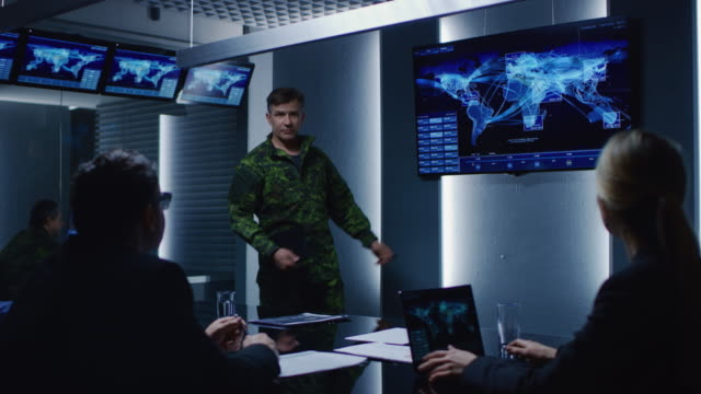 High-Ranking Military Man holds a Briefing to a Team of Government Agents and Politicians, Shows Satellite Surveillance Footage. High-Ranking Military Man holds a Briefing to a Team of Government Agents and Politicians, Shows Satellite Surveillance Footage.  Shot on RED EPIC-W 8K Helium Cinema Camera. army stock videos & royalty-free footage