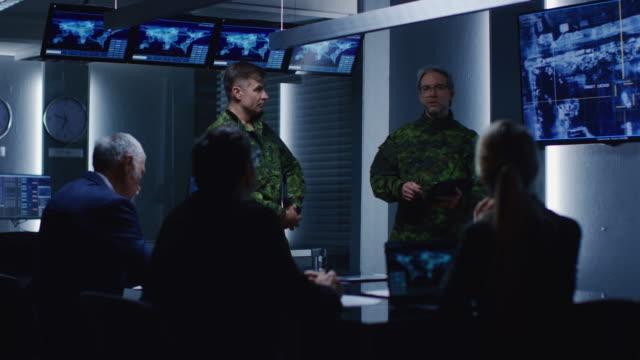 高級軍人は、政府エージェントのチームや政治家、表示映像の次ターゲット車監視衛星に説明会を開催します。 - 軍事点の映像素材/bロール